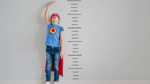 99894299-little-child-is-playing-superhero-kid-is-measuring-the-growth-on-the-background-of-wall-girl-power-c